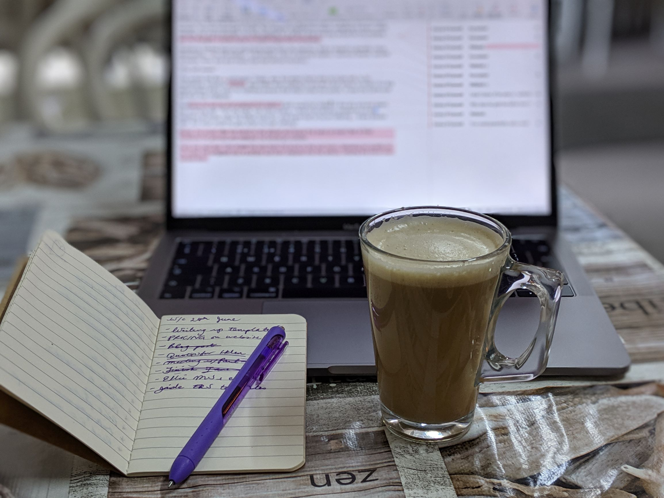 A laptop, a coffee, and an open notebook